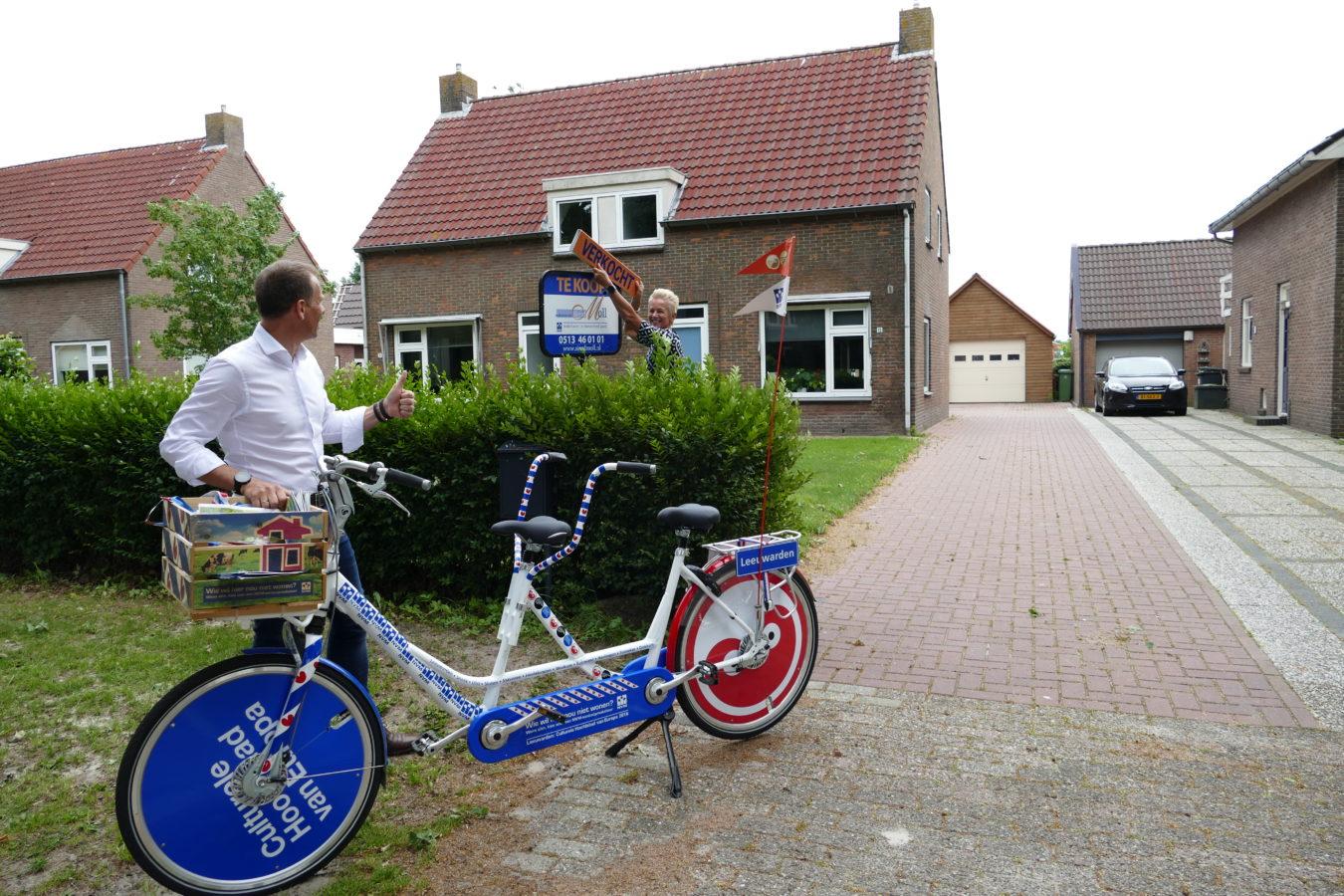 Sierd Moll en Jeannette Schram op de tandem plaatsen een verkocht bord in Jubbega