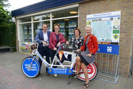 Sierd Moll en Jeannette Schram en Iepie Zijlstra en Petra Moll met de tandem voor het kantoor van Makelaardij Sierd Moll aan de Badweg 30 in Gorredijk